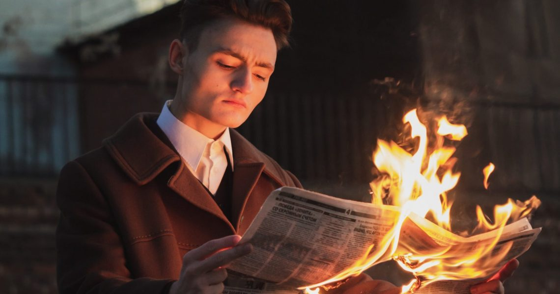 man-reading-burning-newspaper-3278364